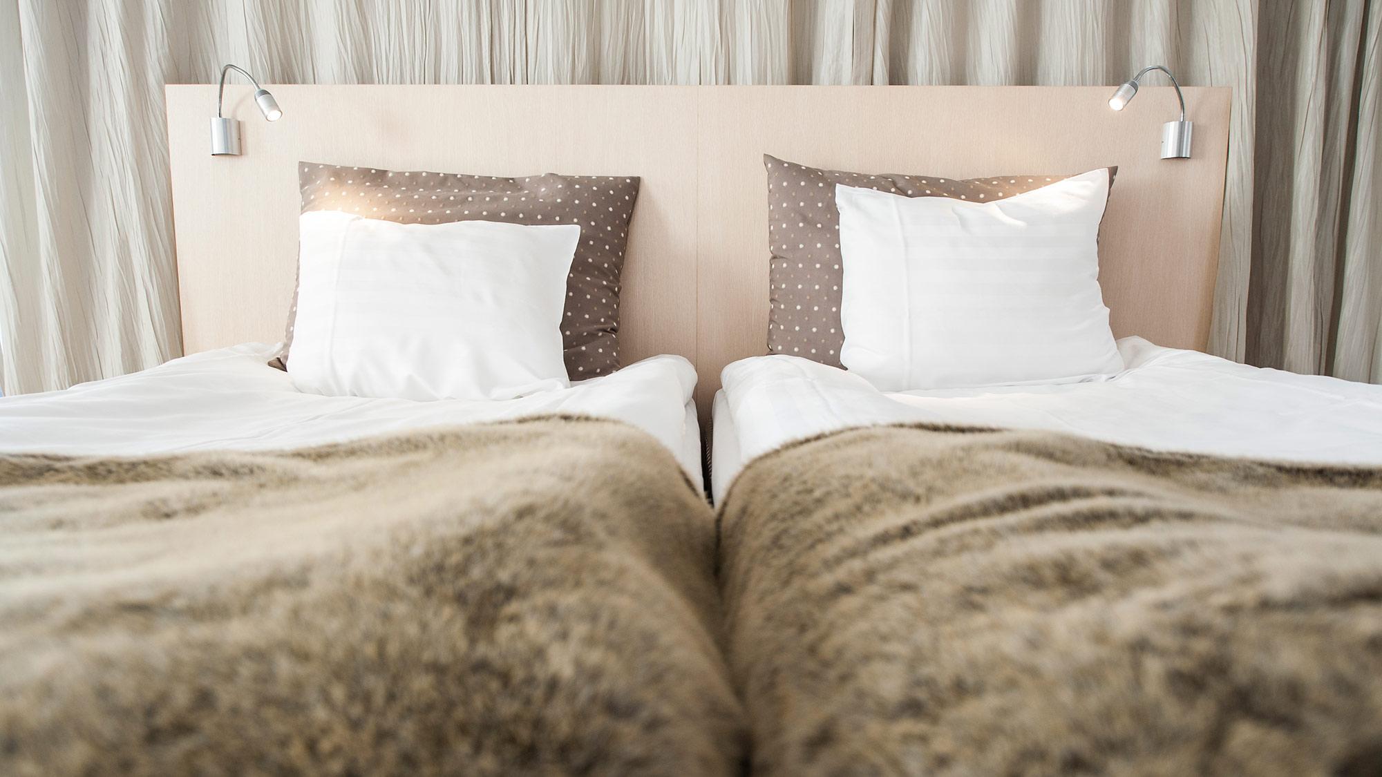 Mukava vuode vaaleasävyisessä Junior Suite huoneessa Hotel Levi Panoramassa