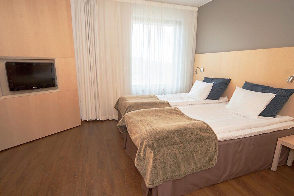 Tilava ja vaalein sävyin sisustettu makuuhuone Standard Sviitissä Hotel Levi Panoramassa