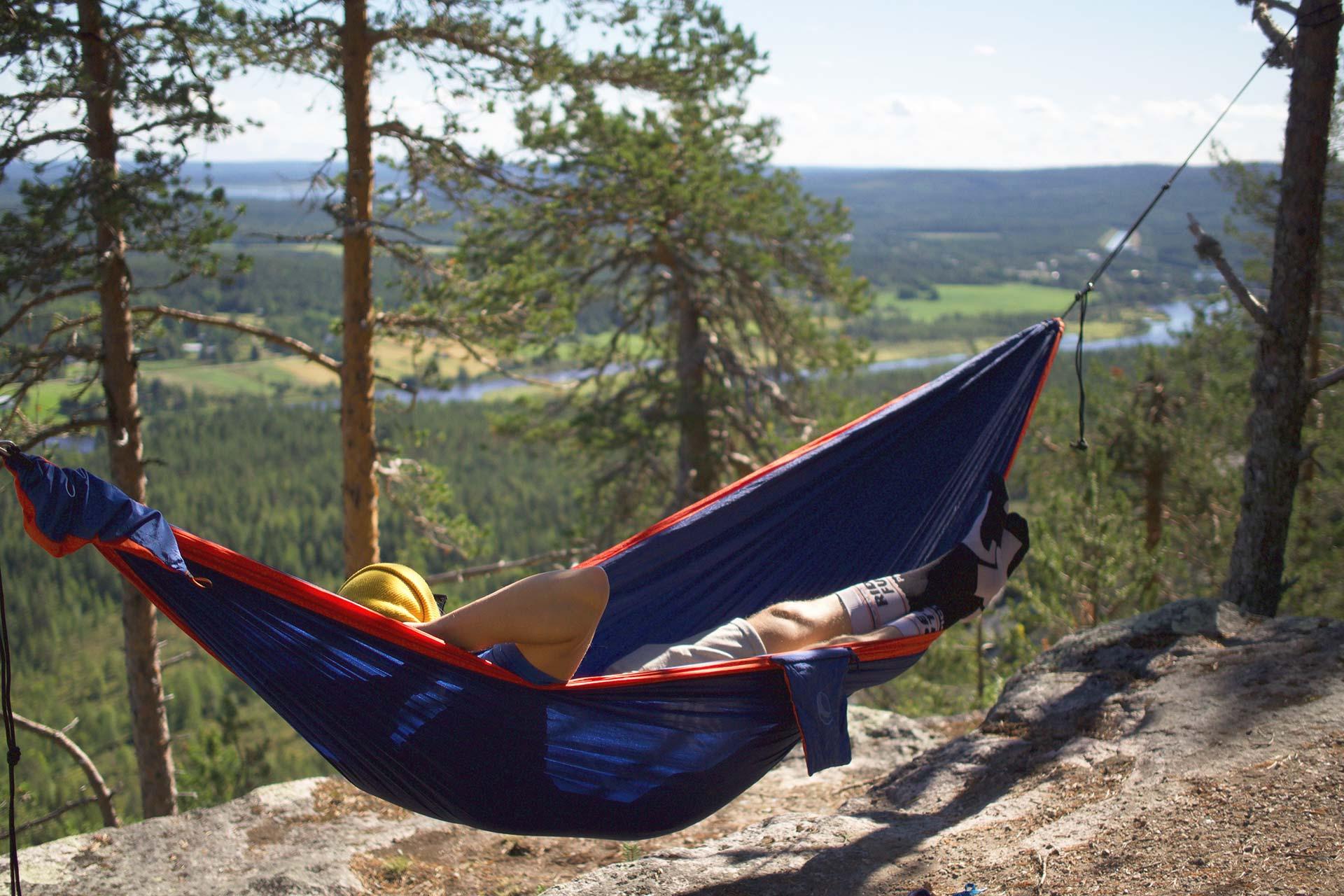 Kesälomailija rentoutumassa riippumatossa Levillä, Lapissa.