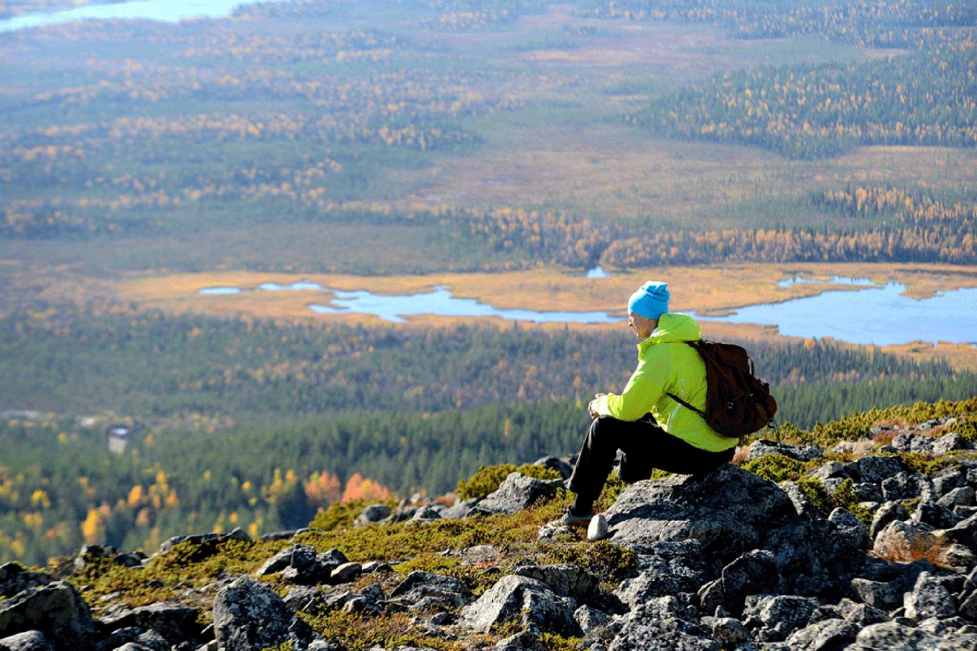 Levitunturin päällä kuvattuna ruskaretkeilijä ihailemassa upeita maisemia.