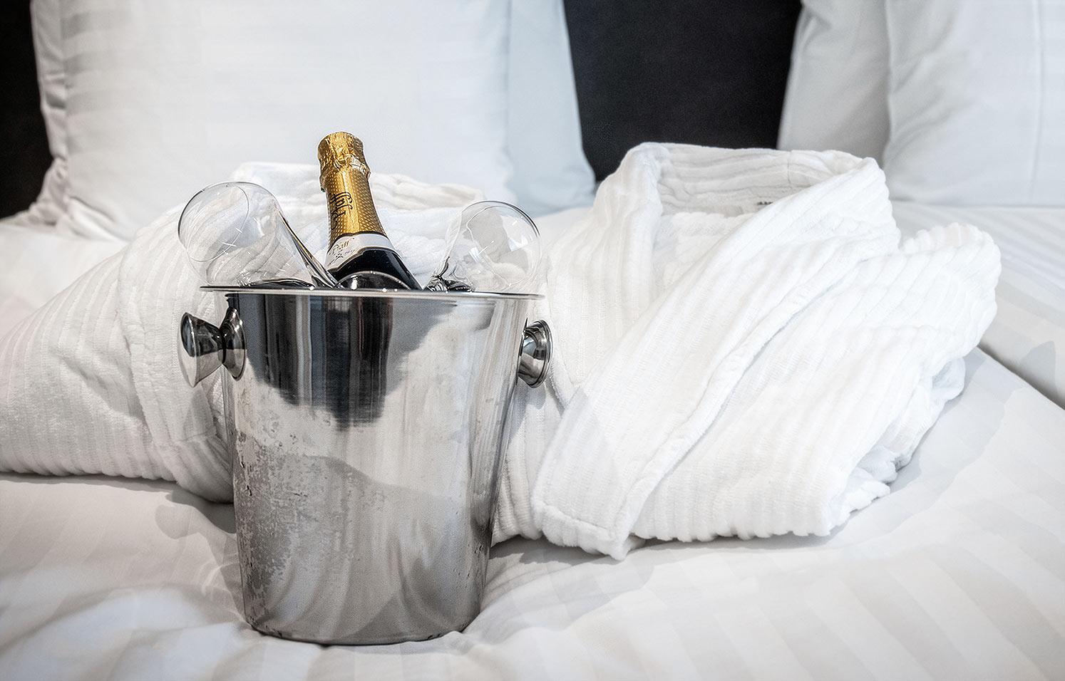 Kuohuviinipullo ja lasit coolerissa hotellin sängyllä.