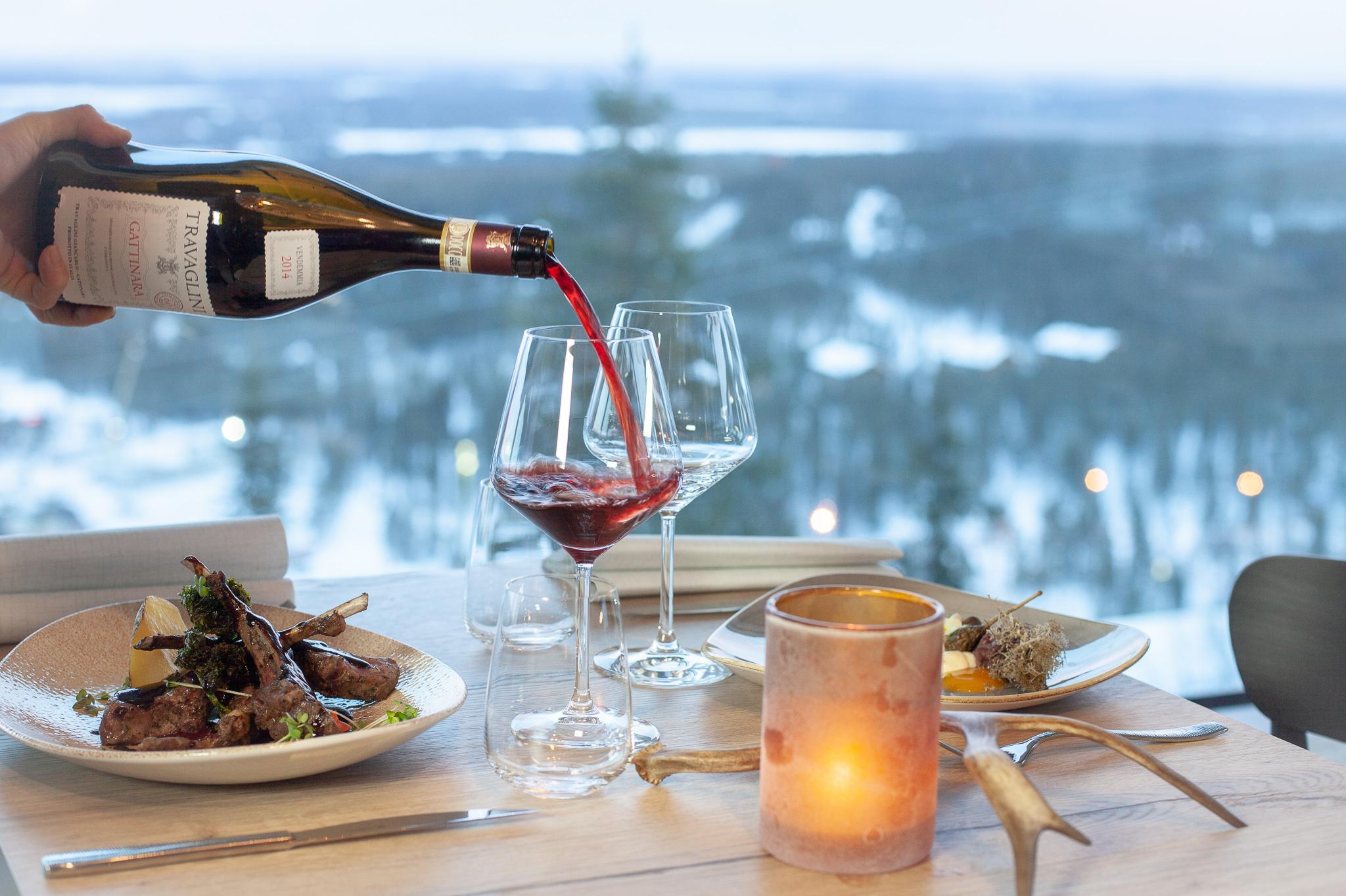 Tarjoilija kaataa illallisella viiniä lasiin upean Lapin maiseman edessä Levillä.
